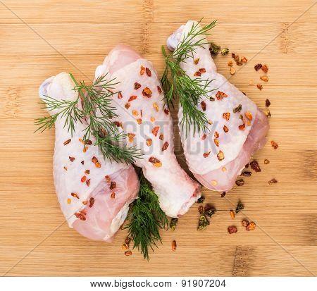 Three Chicken Legs Sprinkled Pepper On Wooden Board