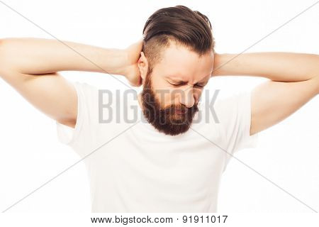 people, life style  and emotional  concept - bearded man covering his ears by hands over white  background