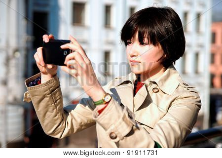Horizontal photo of a girl with a smartphone, taking pictures.