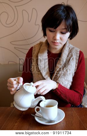 Woman pours tea into a Cup from the kettle.