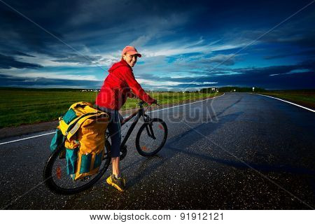 Woman riding loaded bicycle on the wet asphalt road with clouds on the background