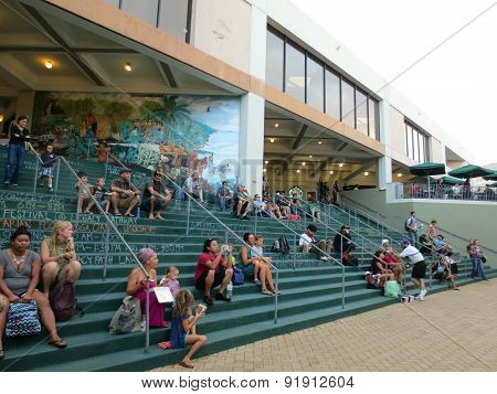 People Sit On Steps As They Watch The Earth Day Concert Festival