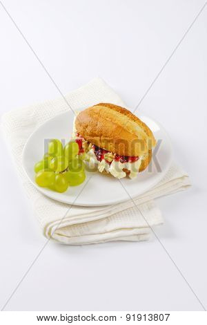 small baguette with brie cheese, walnuts, jam and grapes on white plate