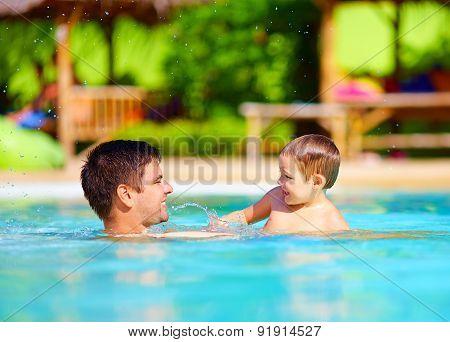 Joyful Father And Son Having Fun In Pool, Summer Holidays