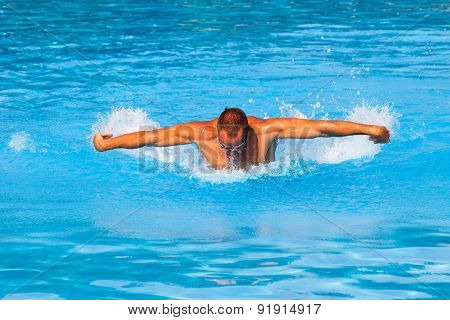 young man swim butterfly style in outdoor swimming pool, sunny summer day