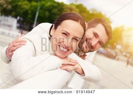 urban photo of smiley young couple in love looking at camera