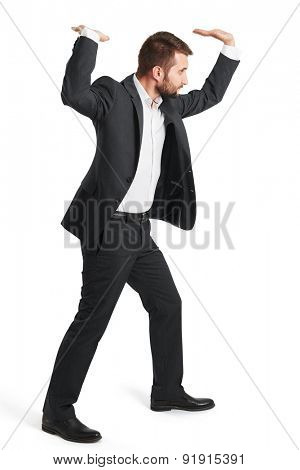 serious businessman in formal wear holding his hands overhead like carrying something. isolated on white background