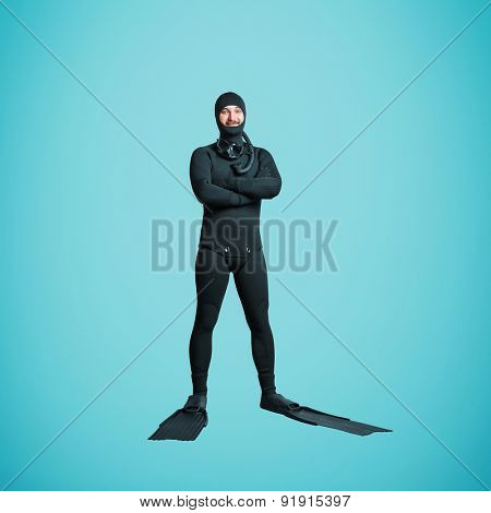 full length portrait of smiley underwater diver in equipment over blue background