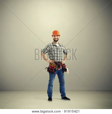 full-length portrait of smiley builder in hard hat and belt with tools over light grey background