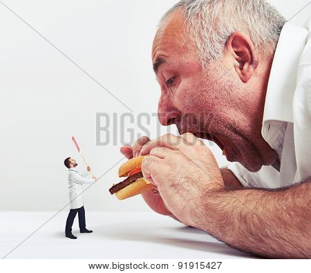 close up photo of man eating burger and small doctor looking at him and protesting against junk food