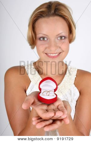 Woman Holding Wedding Rings In Red Box. Focus On Rings