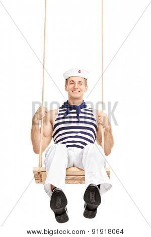 Vertical shot of a cheerful young sailor swinging on a swing and looking at the camera isolated on white background