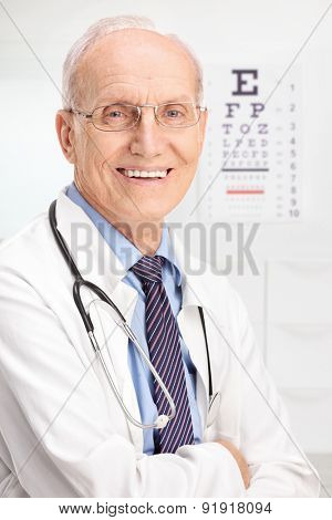 Close up on a mature optician posing in his office with an eyesight test in the background