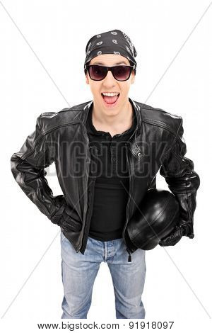 Vertical shot of a joyful young biker with a leather jacket holding a helmet and looking at the camera isolated on white background
