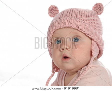 baby girl child lying down on white blanket  pink fashion portrait face studio shot isolated on white caucasian warm hat