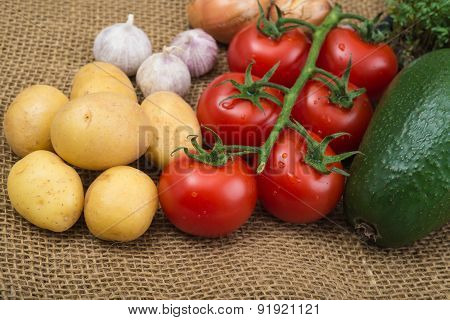 Avocada Cress Tomatoes Onions Garlic Potatoes On Rustic Burlap Background
