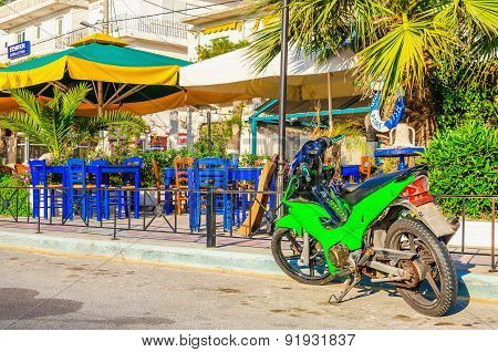 Green motorbike in front of Greek restaurant