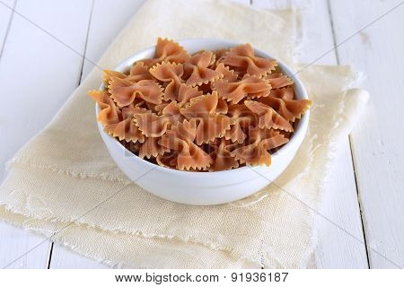 Raw tomato farfalle in a ceramic bowl
