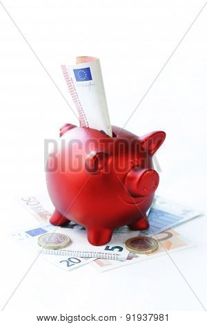 red piggy bank with euro banknotes and coins