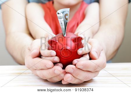 close up of father and son hands holding red piggy bank