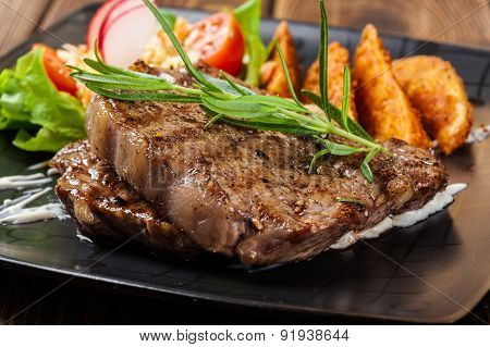 Portion Of Beef Steak Served With Roast Potatoes