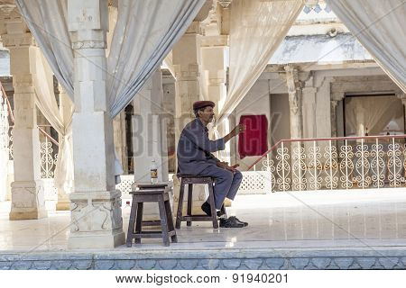 Guard Sits At A Wooden Chair In The City Palace In Udaipur,