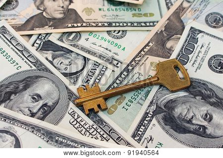 The key on a background of money. The concept of buying or renting a home.