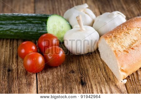 Four Small Tomatoes In Front Of Baguette And Other Vegetable