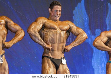 Professional Handsome Male Caucasian Bodybuilder Performing On Stage.