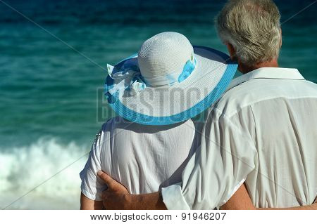 elderly couple walking along the seashore