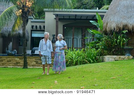 elderly couple standing embracing outdoors