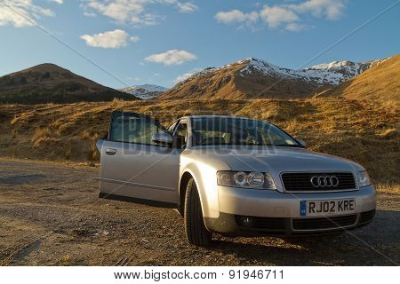 Fort William, Scotland - March 2013: A View Of A Grey Audi Car In Front Of Scenic Scottish Mountains