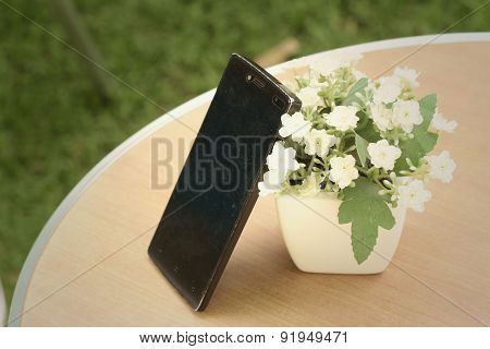 Mobile Phones With Flowers On The Table.