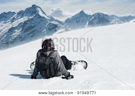 Snowboarder sit at top of mountain