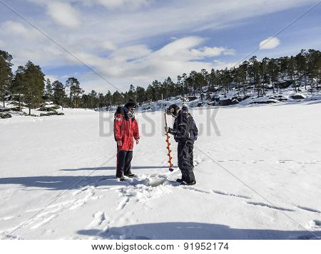 Tourists Do Ice Fishing In Inari