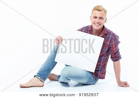 Man sitting on floor with sheet of paper