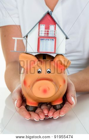 a woman with a house and a piggy bank. proper funding for the home purchase.