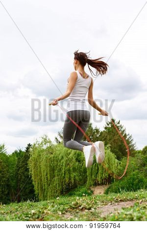 Young slim woman skipping in park