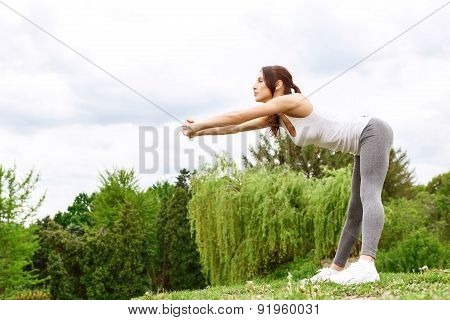 Young sportive woman leaning in park