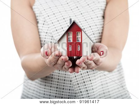 Miniature model house in female hand isolated on white background.