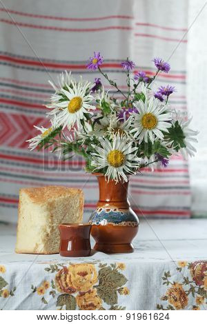 Still Life Of Ceramic Vase And Glass Cut Lilac And White Aster Flowers And Slice Of Yeasted Wheat Br
