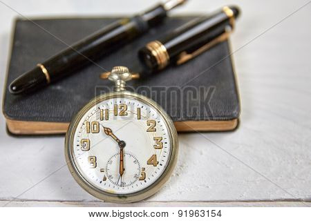 Antique Fountain Pen, Old Calendar And Watch On A White Wooden Table