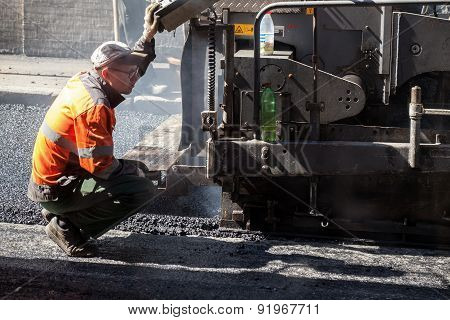 Operator Of Paver Machine Works On A Control Pane