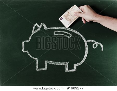 Introducing euro bill in piggybank sketched on blackboard