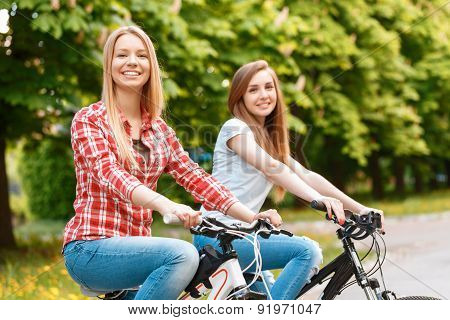 Pretty girls posing with bikes in park