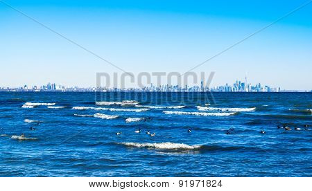 Waves Breaking On Lake With Toronto Skyline On Distant Horizon.