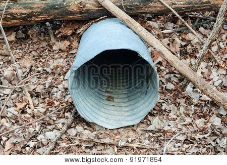 Empty Metal Drain Pipe Under Log On Dead Leaves.