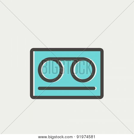 Cassette tape icon thin line for web and mobile, modern minimalistic flat design. Vector icon with dark grey outline and offset colour on light grey background.
