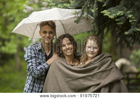 Woman with their adult children, daughter and son, in the Park under an umbrella.