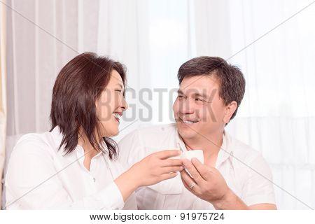 Smiling Asian family drinking tea